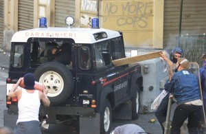 A CARABINIERE POINTS A GUN AS A PROTESTER TRIES TO HURL A FIRE EXTINQUISHER INTO THEIR VEHICLE